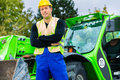 Builder in front of construction machinery or driver standing on building site Stock Photography