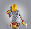 Builder in a helmet with a hammer and a drill Royalty Free Stock Photo