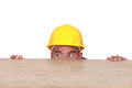 Builder hiding behind a table scared Royalty Free Stock Image