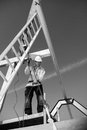 Builder with ladder and winch real construction worker at work on roof construction monochrome Stock Photography