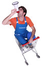 Builder with megaphone sat in shopping trolley Royalty Free Stock Photography