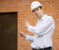 Builder pointing to door in brick wall Royalty Free Stock Photography