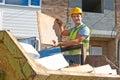 Builder putting waste into rubbish skip puts Stock Image