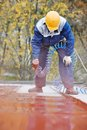 Builder roofer painter worker with pulverizer spraying paint on metal sheet roof Stock Image