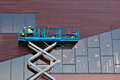 Builder on a scissor lift platform at a construction site men work Royalty Free Stock Image