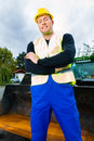 Builder on site in front of construction machinery or driver standing building Royalty Free Stock Photography