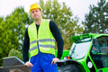 Builder on site in front of construction machinery or driver standing building Stock Images