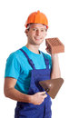 Builder with spatula wearing orange helmet and brick Stock Image