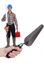 Builder standing on a hand holding a trowel Royalty Free Stock Photos