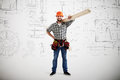Builder in uniform smiley holding long wooden boards over grey wall with prints Stock Images