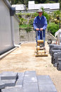 Builder using vibrating roller setting out paving stones pathway construction site westland Stock Images