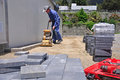 Builder using vibrating roller setting out paving stones pathway construction site westland Royalty Free Stock Photo