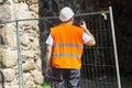 Builder using walkie talkie near fence