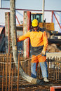 Builder worker at concrete pouring work standing near trailer mounted boom pump on metal rods reinforcement of casting formwork Stock Images