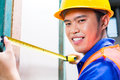 Builder or worker controlling wall on construction site asian indonesian craftsman with hardhat and measure tape checking a of a Royalty Free Stock Photos