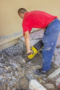 Builder worker with electric jackhammer repairing sidewalk crack Stock Images