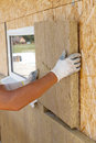 Builder worker installing insulation material on a wall.