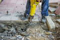 Builder worker with jackhammer repairing sidewalk crack Royalty Free Stock Images