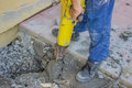 Builder worker with jackhammer repairing sidewalk crack Stock Photo