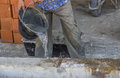 Builder worker wetting concrete with bucket of water before lay the first course blocks by doing this prevent the mortar Royalty Free Stock Images