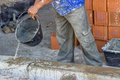 Builder worker wetting concrete with bucket of water