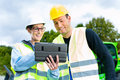 Builders with blueprint on construction site worker and engineer discussing blueprints pad or tablet computer excavator and other Stock Photography
