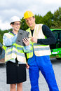 Builders with blueprint on construction site worker and engineer discussing blueprints pad or tablet computer excavator and other Royalty Free Stock Photography