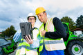 Builders with blueprint on construction site worker and engineer discussing blueprints pad or tablet computer excavator and other Royalty Free Stock Photos