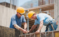Builders cooperating on cement formwork frames Stock Photo