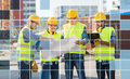 Builders in hardhats and vests with blueprint