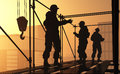 The builders silhouettes of workers against background of city Royalty Free Stock Photography