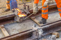 Builders weld and joining segments of the rail tram track construction site Stock Photography