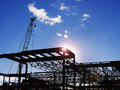 Building construction site new commercial back lit by sun with lens flare as a design element Stock Photos