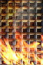 Building in fire apartment with flames coming up to the windows Royalty Free Stock Image