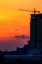 Building under construction and cranes in the sun with silhouette of the aircraft Stock Photo