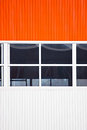 Building wall fragment of made from vertical orange and white panels with windows Stock Image