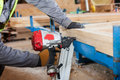Building a wall for frame house.Worker use Framing Nailer to attach wooden beams. Royalty Free Stock Photo