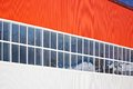 Building wall made from vertical orange and white siding with windows Royalty Free Stock Photo