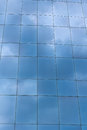 Building windows reflecting sky and glass surface of at tall blue and clouds Royalty Free Stock Image