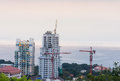 Buildings under construction and cranes the sea Royalty Free Stock Image
