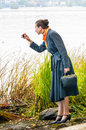 Buisiness woman with digital camera elegant senior business a a bag and an orange scarf taking pictures along the river Stock Photography