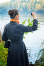Buisiness woman with digital camera elegant senior business a a bag and an orange scarf taking pictures along the river Royalty Free Stock Images