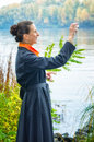 Buisiness woman with digital camera elegant senior business a a bag and an orange scarf taking pictures along the river Stock Images