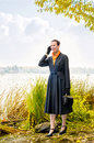 Buisiness woman with phone elegant senior business a mobile a bag and an orange scarf walking along the river under the trees in Stock Photography