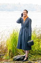 Buisiness woman with phone elegant senior business a mobile a bag and an orange scarf walking along the river under the trees in Stock Photos