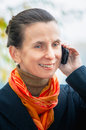 Buisiness woman with phone portrait of an elegant senior business a mobile and an orange scarf under the trees in autumn Stock Images