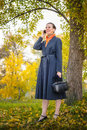 Buisiness woman with phone senior business a mobile a bag and an orange scarf walking in the park under the trees in autumn Royalty Free Stock Images