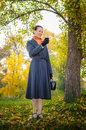 Buisiness woman with phone senior business a mobile a bag and an orange scarf walking in the park under the trees in autumn Royalty Free Stock Photography