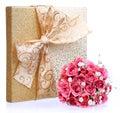 Bukett av rosa rosor och guld gåvaasken som isoleras på vit Arkivfoton