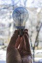 Bulb in a man hand with a wind turbine inside Royalty Free Stock Photo